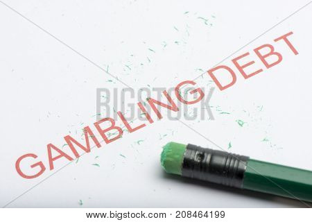 Word 'gambling Debt' With Worn Pencil Eraser And Shavings