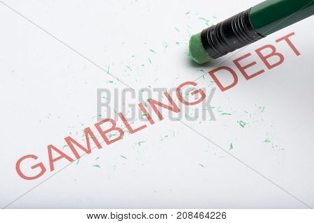 Pencil Erasing The Word 'gambling Debt' On Paper