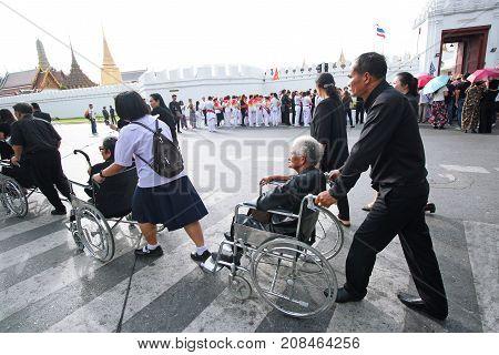 BANGKOK-THAILAND : People help senior on wheelchair to devotions for funeral of King Bhumibol Adulyadej in Wat Phra Kaew on January 3 2017