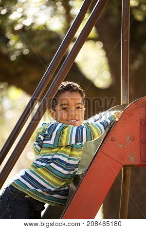 Hispanic little boy playing at the park.