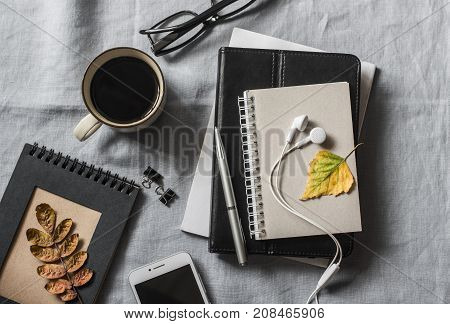 Home workplace with a business education education accessories. Notepad tablet phone earbuds pen glasses coffee on grey background top view. Flat lay