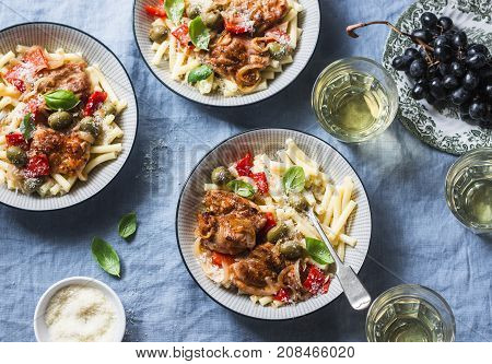 Italian food table. Pasta with slow cooker chicken with olives and sweet peppers white wine. On a blue background top view