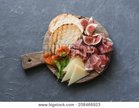 Delicious appetizers for wine or a snack - prosciutto figs bread cheese on a rustic wooden cutting board. On a gray background top view