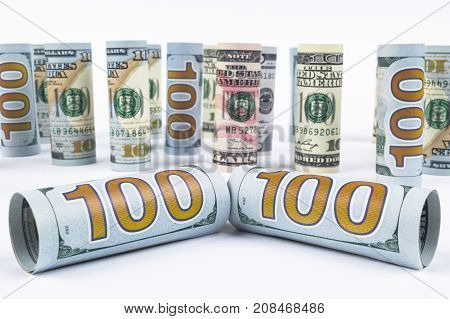Dollar. Dollar banknotes roll in other positions. American US currency on white board. American dollar banknote rolls in all denominations on white background