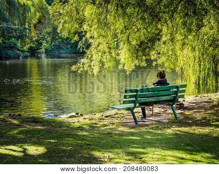 Woman sitting on a bench overlooking the lake under weeping willow
