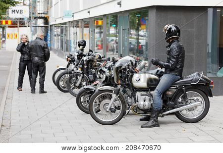 STOCKHOLM SWEDEN - SEPT 02 2017: Man in jeans and leather jacket sitting on retro motorcycle at the Mods vs Rockers event at the Saint Eriks bridge Stockholm Sweden September 02 2017