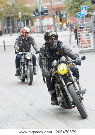 STOCKHOLM SWEDEN - SEPT 02 2017: Tough mc drivers in leather clothes on retro motorcycles at the Mods vs Rockers event at the Saint Eriks bridge Stockholm Sweden September 02 2017
