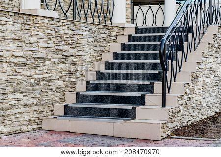 Fragment of modern stairs design, porch with metal railings and trim stone