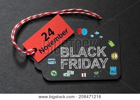 Black Friday text on a black tag with red and white twine