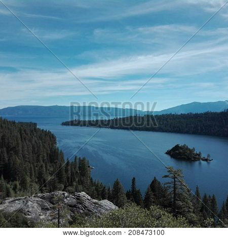 Lake Tahoe in California surrounded by trees with small island in the middle in the summer.