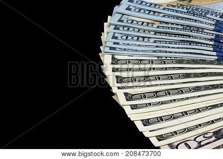 Stack of one hundred dollar bills. Stack of cash money in hundred dollar banknotes. Heap of hundred dollar bills isolated on black background