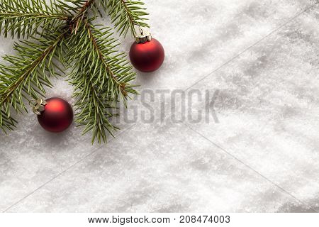 Christmas Baubles And Branch Of Spruce Tree On Snow
