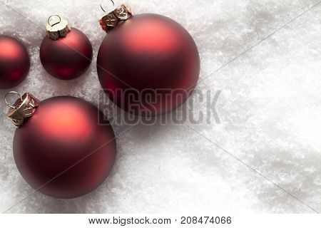 Christmas background - red baubles on snow