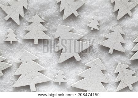 Many white wooden Christmas trees on snow