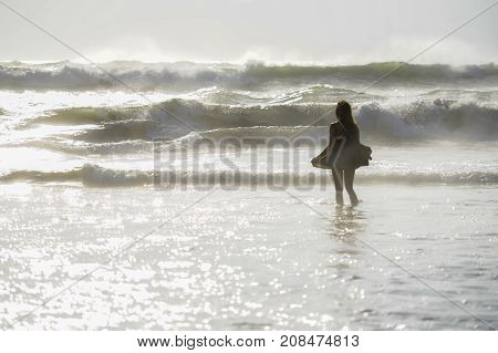 back light shinny portrait of young happy Asian woman relaxed looking at wild sea waves on sunset tropical beach in Bali Asia enjoying sun and sea breeze in relax holiday and summer vacation trip