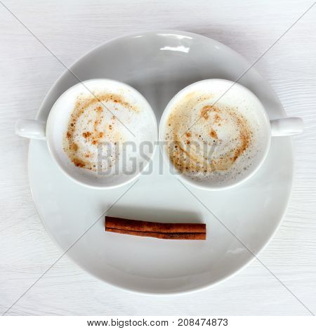 Two white cups with frothy coffee and cinnamon stick on a plate top view / double invigorating cappuccino