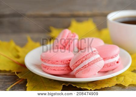 French cakes macaron or macaroon. Light pink macarons on a white plate, a cup of coffee, yellow leaves on a vintage wooden background. Fall snack concept. Closeup