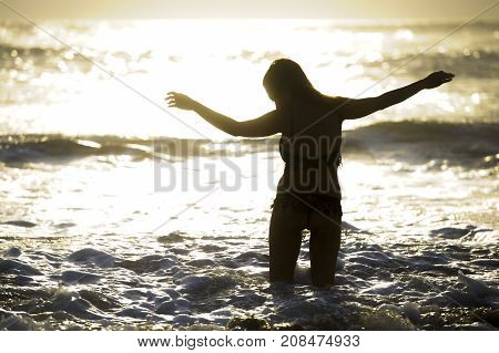 back light shinny silhouette of young happy Asian woman relaxed looking at wild sea waves on sunset tropical beach in Bali Asia enjoying sun and sea breeze in relax holiday and summer vacation trip