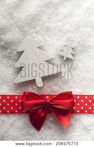 Wooden Christmas trees red bow and ribbon on snow