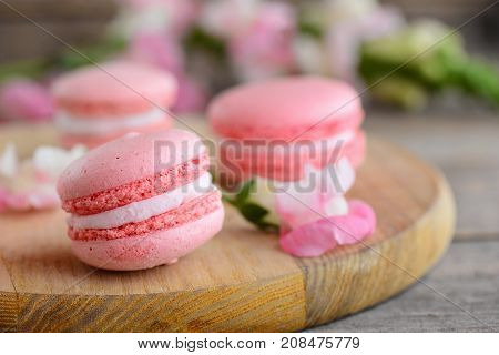 French cakes macaroons. Light pink round macaroons and flowers on a wooden board. Vintage wooden background. Sweets photo. Closeup