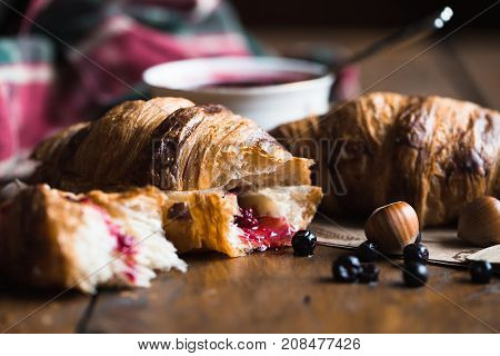 Tasty buttery croissants on old wooden table.