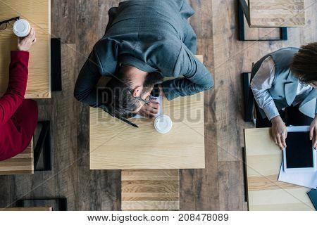 Businessman Sleeping In Cafe