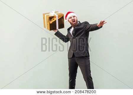 Catch your gift! Young adult well dressed bearded man swung and wants to throw off your gift box isolated on gray background. Studio shot