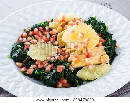 Chicken breast salad with spinach white pomegranate and grapefruit. Light lunch. Festive winter meal