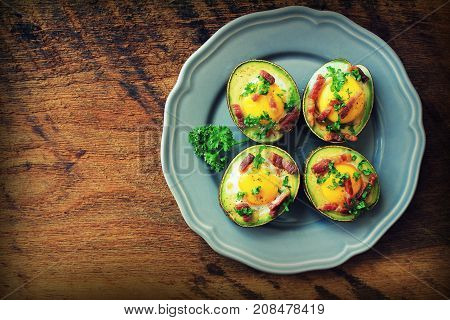 Avocado Egg Boats with bacon on dark wooden background. Top view.