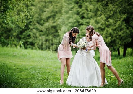 Attractive Bride Posing And Having Fun With Two Her Bridesmaids In The Park On A Sunny Spring Weddin