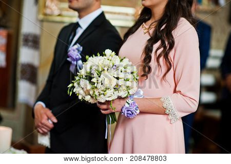 Close-up Photo Of A Bridesmaid Holding A Bouquet Of Flowers In The Church During The Wedding Ceremon