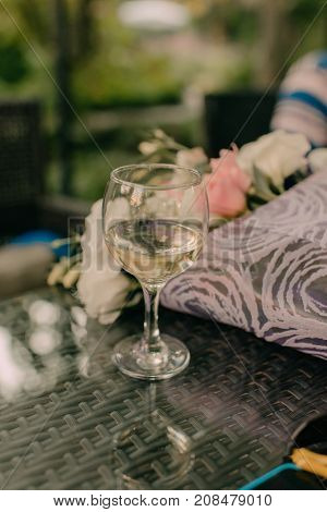 a glass of white wine on a glass table