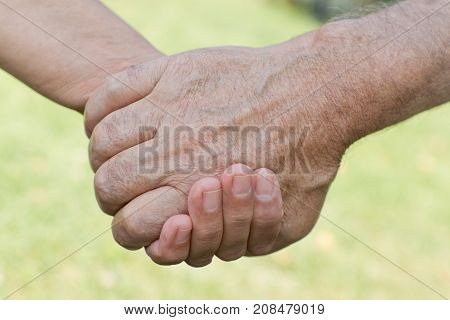 Teenage grandson holding his grandfather's hand and giving helping hand