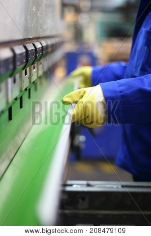 operator bending metal sheet by sheet bending machine, production work process in fabricated factory by worker, manual or semi auto processing.