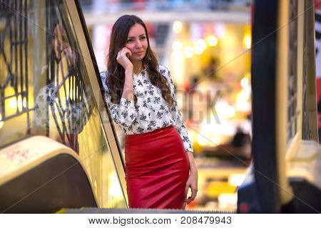 The girl is walking along the escalator and talking on the phone with a smile leaning on the rail. A woman in a red leather skirt and a blouse with patterns in the Moscow office.