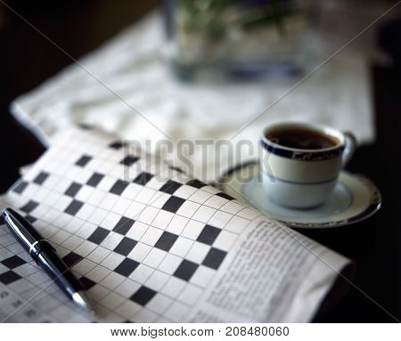 crossword puzzle with pen and black coffe