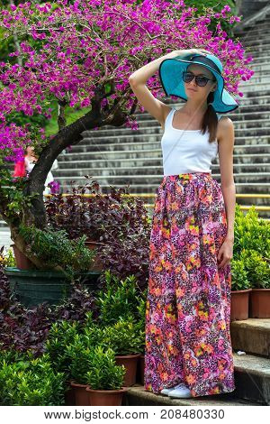 A girl in azure hat with fields a white tshirt and a long pink skirt against the background of a flower tree. A woman in Sanya, Hainan, China.