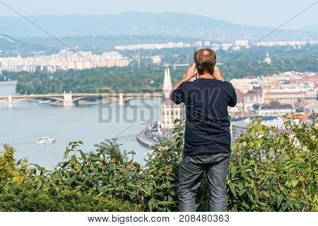 Caucasian male standing in green bushes up high at a viewpoint to take a panoramic picture Budapest below.