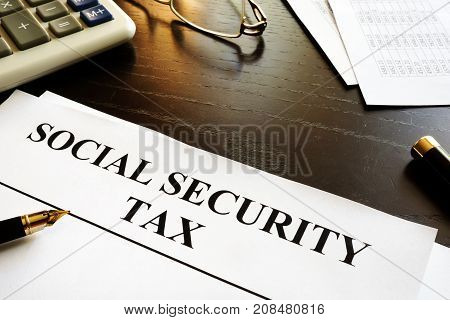 Papers with title social security tax and calculator.