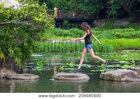 Girl jumping on stones in the lake. Jumping woman in the Yanoda National Park, Hainan, China.