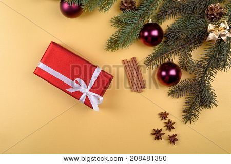 Christmas Background With Red Gift Box, Fir Tree Branches With Glass Balls, Pine Cones, Cinnamon Sti