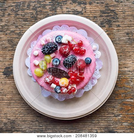 Sweet cheese cake with fresh berries and yoghurt cream. Delicious raspberry cake with fresh strawberries, raspberries, blueberry, currants and blackberry fruits on rustic wooden background