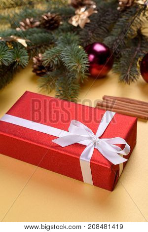 Christmas Background With Red Gift Box, Fir Tree Branches With Glass Balls, Pine Cones And Cinnamon