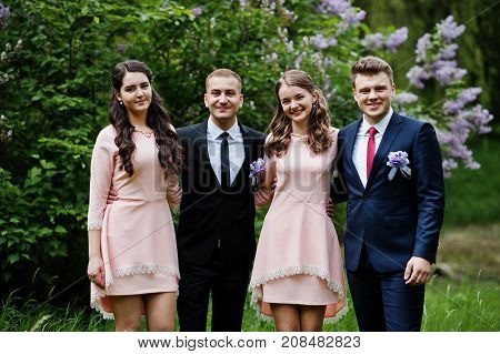 Bridesmaids In Pink Dresses Posing With Handsome Groomsmen In Tuxedos In The Park With Blossoming Tr