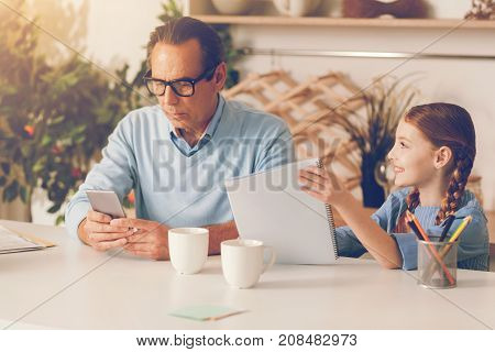 Ignoring attitude. Friendly young lady sitting next to her serious father and asking him to look at her drawing while he completely ignoring her and refuses to check the masterpiece out.