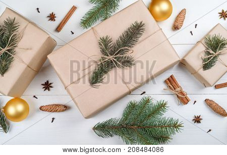 Christmas Background With Gift Boxes Wrapped In Kraft Paper, Fir Tree Branches, Golden Glass Balls,