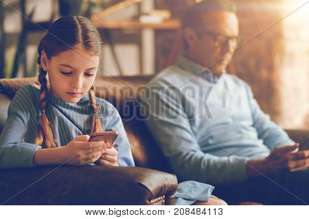 Absence of interest. Selective focus on a young lady with braids sitting on a sofa together with her dad while both using their phones and ignoring each other.