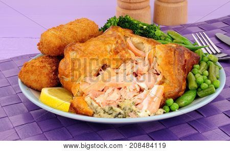 Pink salmon wrapped in puff pastry meal with potato croquettes and vegetables