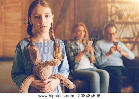 I want my parents back. Waist up shot of a sad little girl with braids embracing her favorite toy and looking into the camera with eyes full of sadness while her parents using their phones