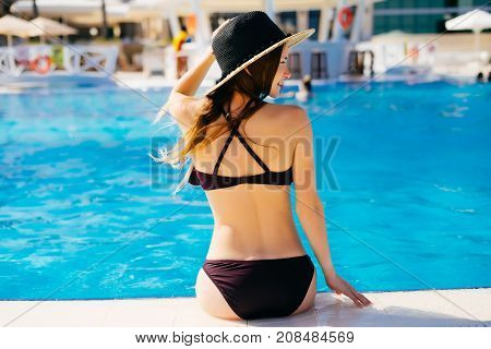 Back view of fashion woman on summer vacation relaxing at luxury resort spa poolside. Young fashionable lady wearing sun hat